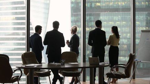 Diverse multi ethnic employees group stand separately talking at work in modern boardroom skyscraper office, racial segregation discrimination prejudice problem at workplace concept, rear back view