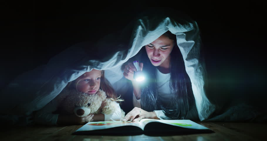 Slow motion of young mother is reading a goodnight story to her little daughter in the dark illuminating with a torch under the blanket. Concept of family, childhood, love, health, education | Shutterstock HD Video #1022540224
