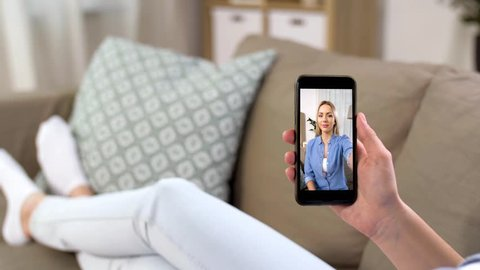 technology, communication and people concept - woman on sofa having video call with friend on smartphone at home