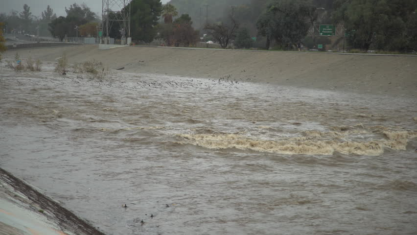 Los Angeles River flows fast after a day of heavy rains in Los Angeles, California.    Shutterstock HD Video #1022577994