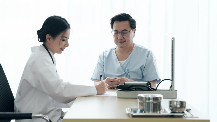 Doctor with patient. Young female medical doctor talking to a senior patient at hospital. Taking notes. Senior care medical and insurance concept. | Shutterstock HD Video #1022583424