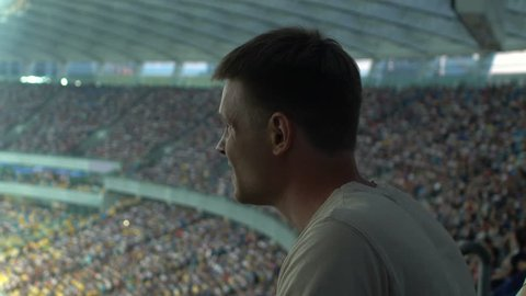 Male spectator watching sport game at stadium, concentrated and agitated, worry