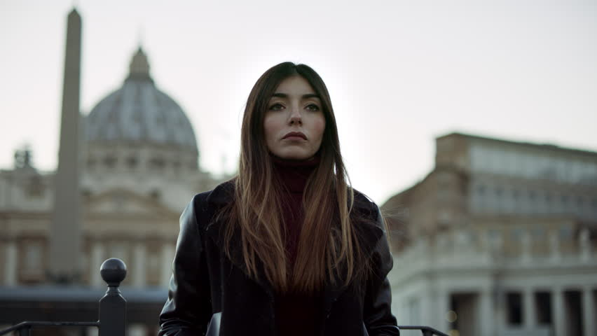 Fashionable Italian woman walking in St. Peter's Square in the Vatican at Christmas, with soft sunset natural light. Medium shot on 4k RED camera on gimbal.