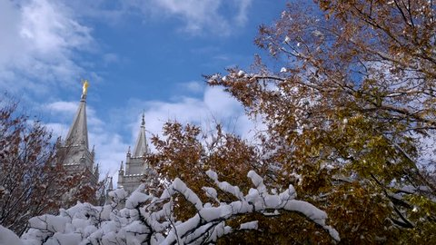 The LDS Mormon Temple in Salt Lake City, Utah after a snow storm on a clear morning - panning left