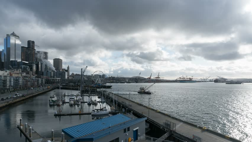 Time lapse of moving dark clouds and stormy sky over Seattle Washington downtown city skyline along Pier 66 and Puget Sound marina waterfront 4k ultra high definition movie 3840x2160