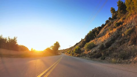 Car travel gopro point of view across mediterranean coastline nature, golden shining sun, asphalt road POV drive