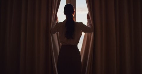 business woman opening curtains in hotel room looking out window fresh new day successful independent female planning ahead at sunrise