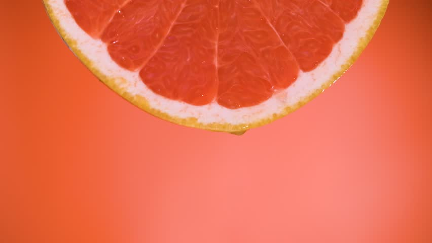 Closeup juice droplets flowing in glass from grapefruit or red sicilian orange #1022702974