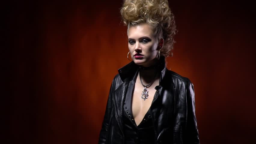 Blonde rocker girl with amazing hairstyle, angrily takes off her jacket and puts it on her shoulder