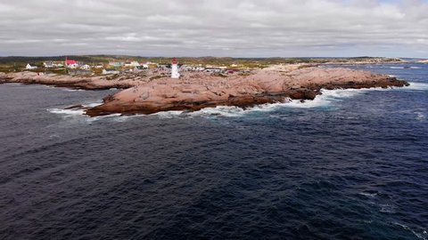 Aerial, drone shot, above the sea, around a lighthouse, on the coast of Nova scotia, near peggy's cove, on a windy and cloudy, autumn day, in Canada