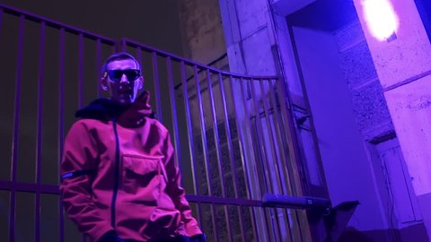 Attractive slim caucasian charismatic dark-haired guy dressed in red sportive jacket with hood is actively rapping and looking at camera at street next to fence with metallic bars.
