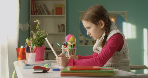 Pretty Little School Kid Wants to Do Homework on the Tablet at the Table at Home on Sunny Day