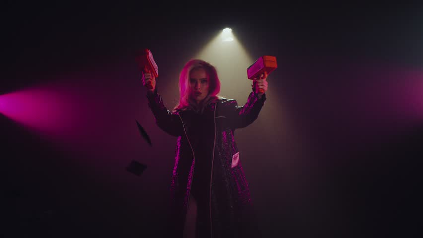 Charming cocky woman shooting two money guns in a studio room with smoke. Dollar bills flying around in a room. Shoot with RED RAVEN camera. | Shutterstock HD Video #1022772904
