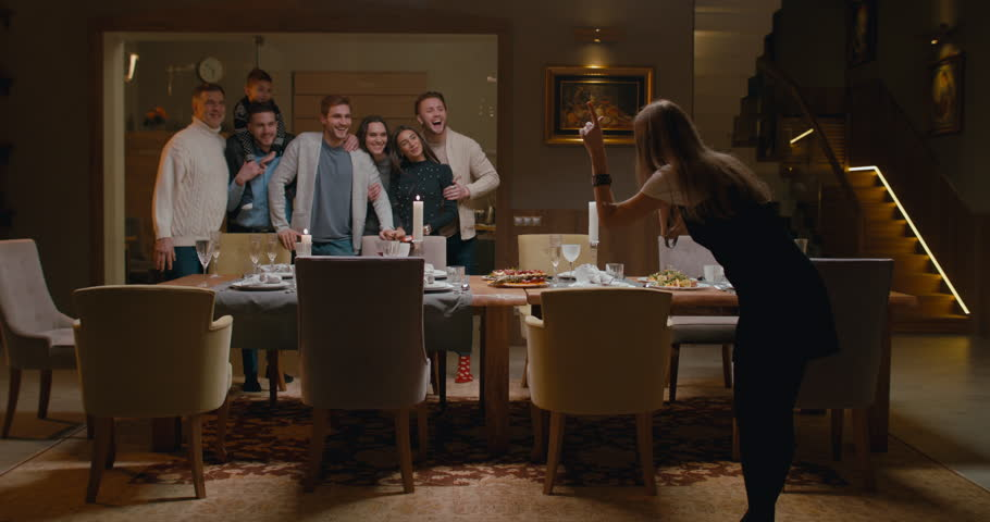 WS Large family or group of friends gather around near dining table to make a photo. 4K UHD 60 FPS SLOW MOTION Blackmagic RAW | Shutterstock HD Video #1022808004
