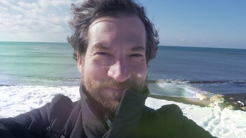 Happy man showing snow on beach in winter in north of Europe