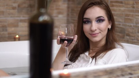 Portrait of cute young woman in white shirt with wine glass taking a bath. Sensual girl enjoying in the bathroom with burning candles. Bottle in the foreground blurred.