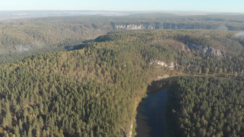 Slow aerial flight backwards over a gentle mountain river, pine forest, clouds. | Shutterstock HD Video #1022858554