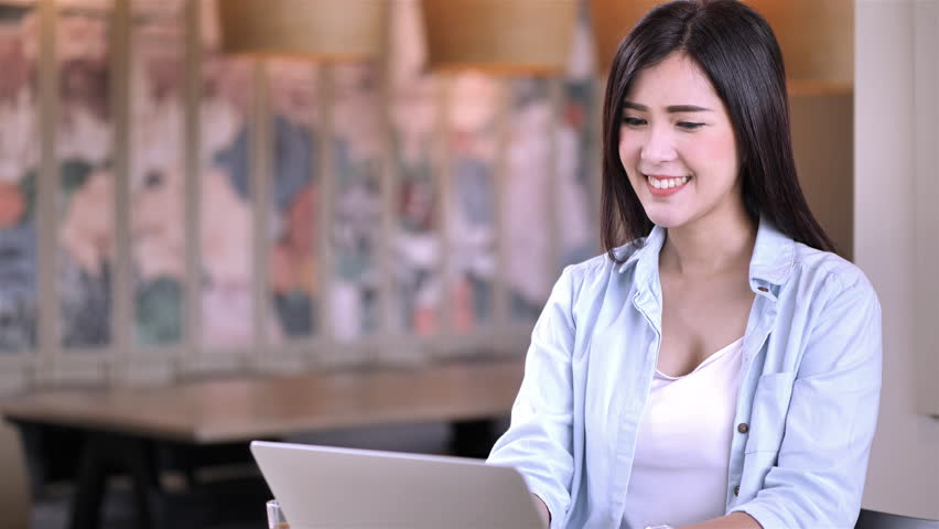 Beautiful Asian girl working at coffee shop connected on laptop computer Hand on keyboard. education or technology or startup business concept. Slow Motion | Shutterstock HD Video #1022861944