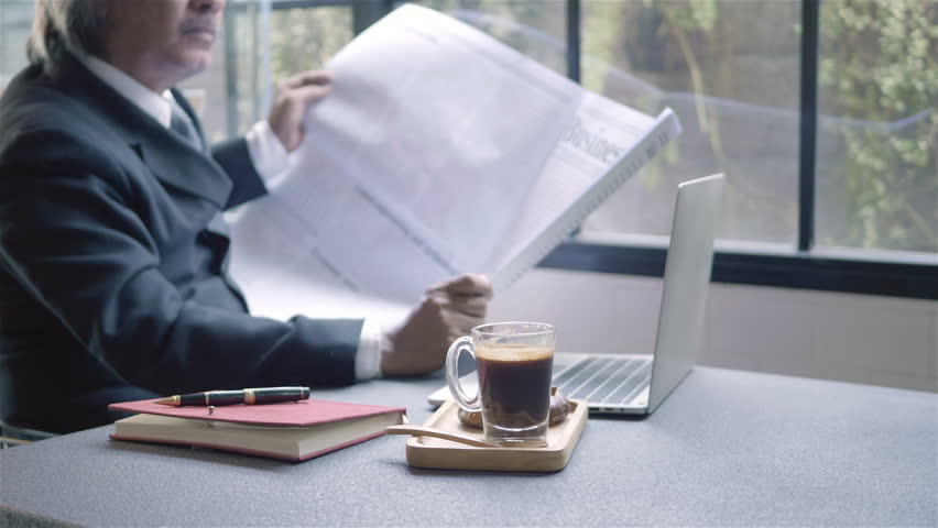 Senior businessman with computer laptop. He spend their free time reading book and drinking coffee, sit in a coffee shop, morning. | Shutterstock HD Video #1022861974