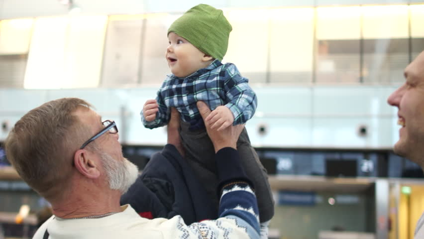 Grandpa first saw his little grandson. Mature man takes the hands of the baby. Grandfather, son and grandson. Meeting at the airport
