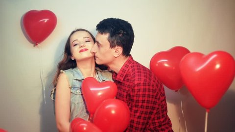Man makes present to his lovely sweetheart girl. Lover's valentine day. Valentine Couple. Man gives to his girlfriend sweets at heart box.  Background red balloons hearts. Man kiss his girl.