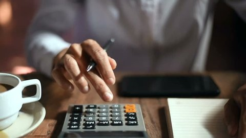 Close up of businesswoman or accountant hand holding pen working on calculator to calculate business data, accountancy document and laptop computer at office, business concept