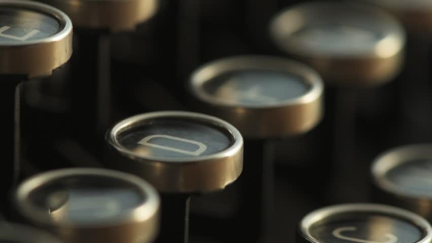 Slow motion of finger typing typewriter key, extreme close up
