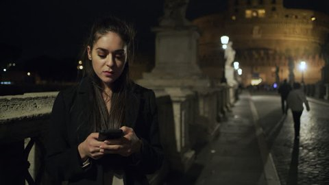 On the St Angelo Bridge at night, a young Italian woman stands looking down at her phone while people pass by her. Wide shot on 8k helium RED camera.