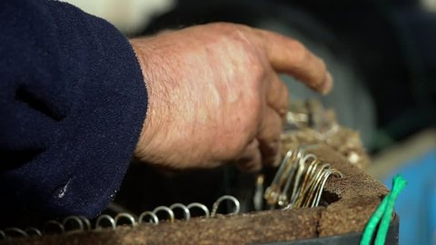 Close-up male hand puts bait on crochet hooks Fishing Seine, hooks close-up. For sea fishing