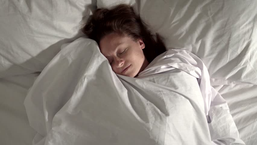 Beautiful woman smiles in her sleep. Shooting from above. Close-up. | Shutterstock HD Video #1022984044