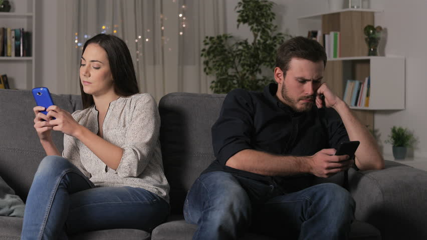 Angry couple using their smartphones after argument sitting on a couch at home in the night | Shutterstock HD Video #1022987134