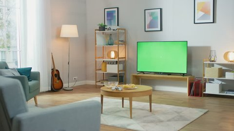 Cozy Living Room with Stylish Furniture and Design, Green Chroma Key TV in the Middle of the Room. Zoom In Camera Shot.