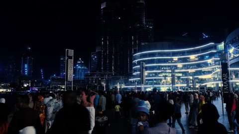 DUBAI UNITED ARAB EMIRATES - JANUARY 11 2019: Crowd of tourists at night in the square near the dancing fountain, the famous world shopping center Dubai Mall and the Burj Khalifa Tower.