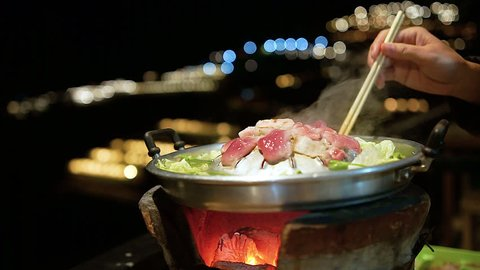 the pan for Thai Barbecue or Moo Kra Ta on top of Thai traditional stove with a woman hand holding chopsticks.