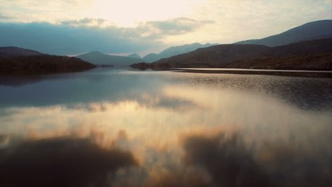 Aerial drone footage of lake and mountains against sky. Fast tracking shot of rippled water and on lake. Reflection of clouds is falling in water. Filmed from surface level perspective. HD 1080 video.