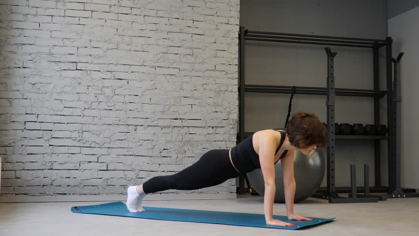 Side view of young athletic caucasian woman in sports clothing keeping plank position while exercising indoors in gym #1023078664