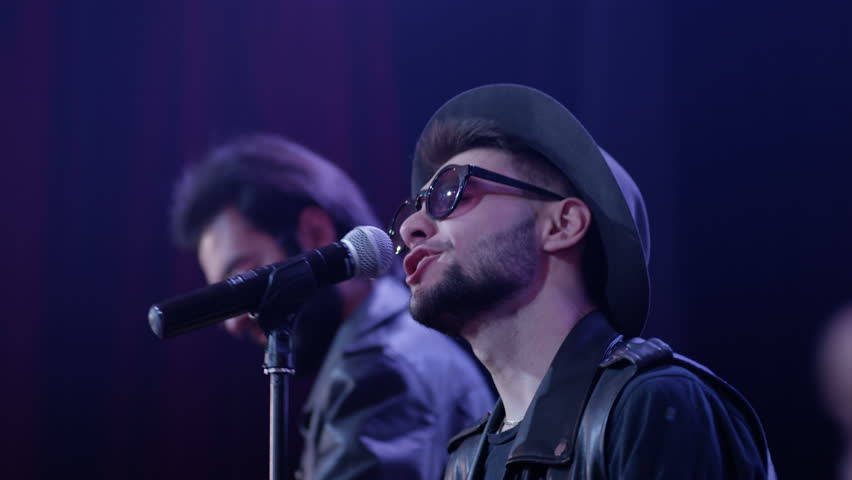 Stylish group of young men musician or rock band playing on bass, lead guitar and singing with crazy emotions and movements . Shot on RED HELIUM Cinema Camera. | Shutterstock HD Video #1023089794