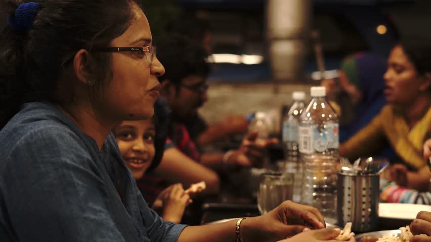 Kuala Lumpur, Malaysia - December 24th, 2018 : Happy Indian family eating together at mamak restaurant at night.