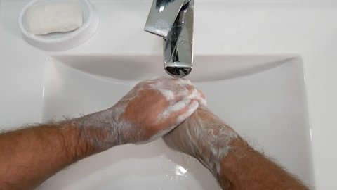 Man Washing Hard His Hands with a Lot of Soap in Bathroom Sink With Chill Water