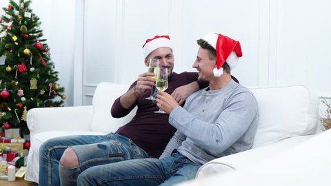 Happy gay male couple celebrating Chritsmas at home sitting on the couch drinking champagne