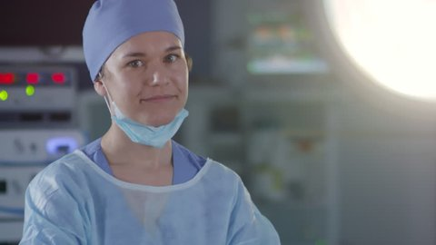 Portrait of young Caucasian female surgeon or doctor standing in operating room and smiling at camera, medium shot