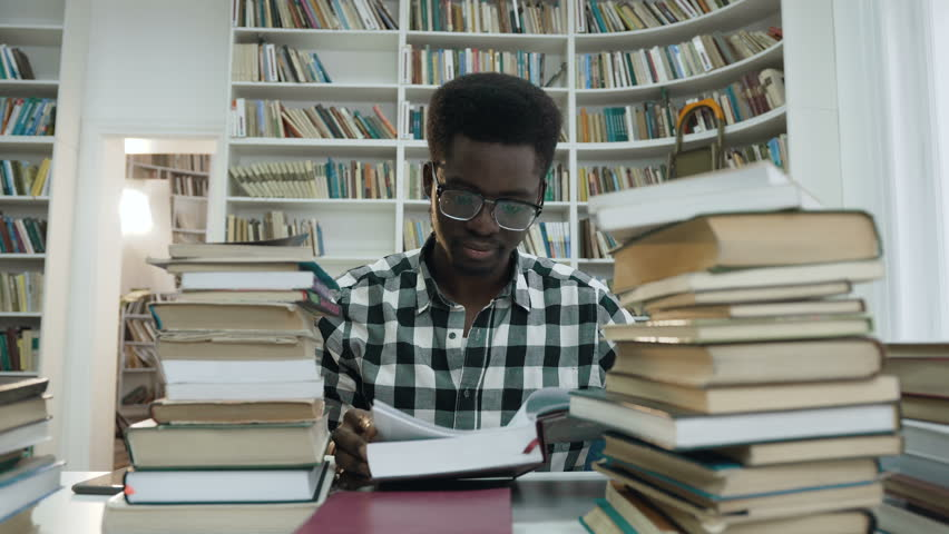 Portrait of african young man in shirt with glasses reading book while sitting in the light modern library. Dolly shot. | Shutterstock HD Video #1023162934