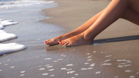 Sea waves washing over tanned female feet. Beautiful young woman relaxing on coast during summer vacation. Legs of girl lying on the beach on a sunny day. Close up Slow motion