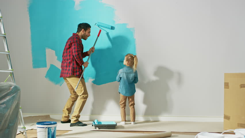 Young Father is Showing How to Paint Walls to Cute Small Daughter. They Paint with Rollers that are Covered in Light Blue Paint. Room Renovations at Home.