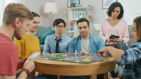 Diverse Group of Guys and Girls Playing in a Strategic Board Game with Cards and Dice. Cozy Living Room in a Daytime