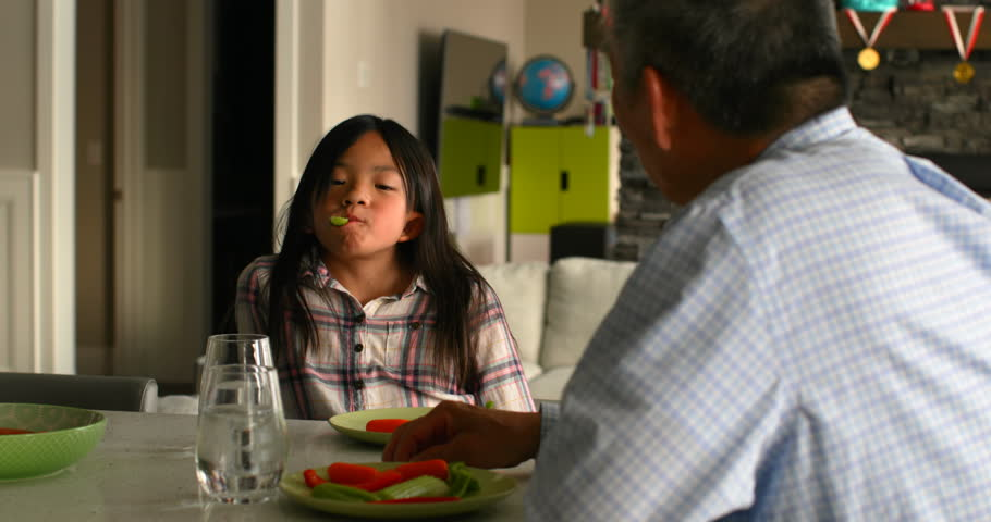 Cute Asian granddaughter and old senior grandfather eating food in a comfortable home. Food plate and glass of water on dining table  | Shutterstock HD Video #1023204124