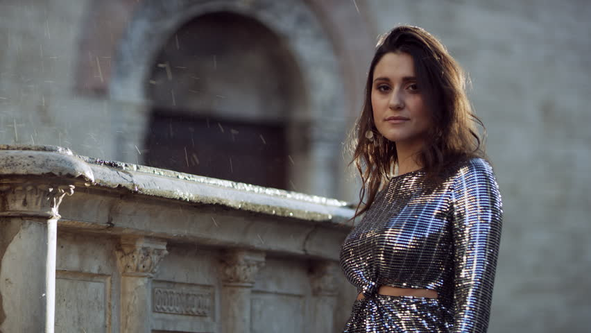 Beautiful Italian fashion model posing in her dress in front of an old fountain in Bevagna, with bright natural light. Wide shot on 8k helium RED camera. | Shutterstock HD Video #1023218794