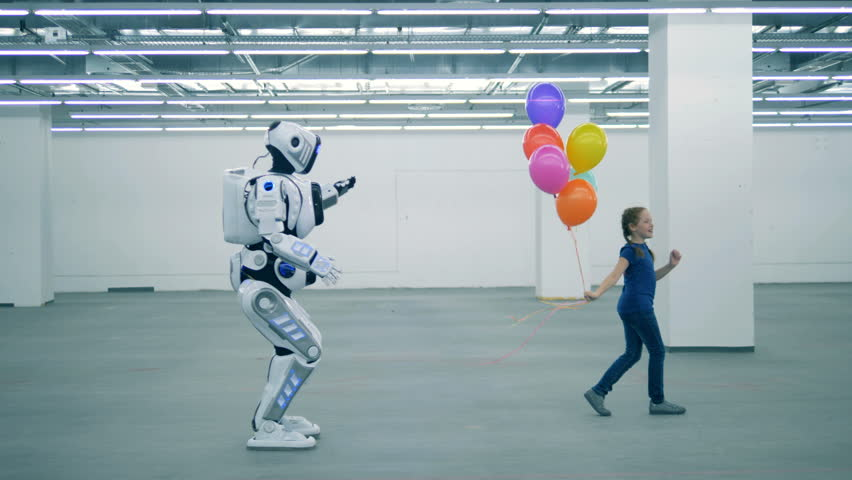 A girl with balloons is dancing and a manlike robot is coming towards her | Shutterstock HD Video #1023238684