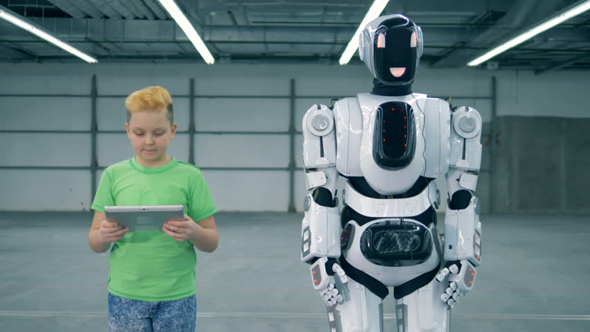Boy with a tablet is manipulating a robot into walking | Shutterstock HD Video #1023238894