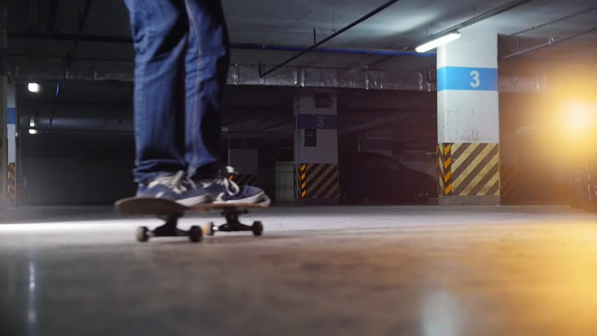 Underground parking lot. A young man skateboarding. Making a spin and continue skating | Shutterstock HD Video #1023275374